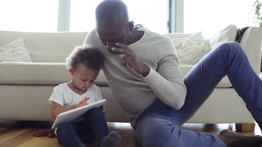 Afro-american father with little daughter at home holding tablet. Royalty-Free Stock Footage #28082947