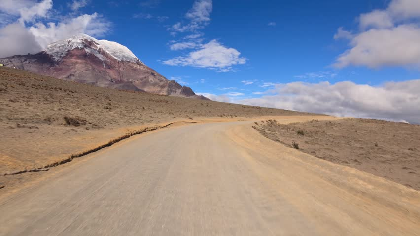 Driving thru Ecuadorian Andes on the way up to Chimborazo refugee at 5000m altitude. You can see the volcano and the car speeding on a bumpy road.