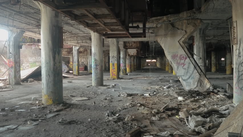 CLOSE UP: Scary halls in decaying abandoned old Fisher Body Plant automotive factory, Detroit, United States. Spooky dilapidated garage in big haunted industrial building after the financial crisis