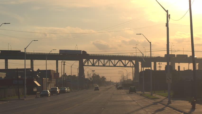 DETROIT, UNITED STATES - OCTOBER 17 2016: Semi trucks driving over the overpass, transporting goods across the busy multiple lane highway full of cars at golden sunrise in industrial city Detroit