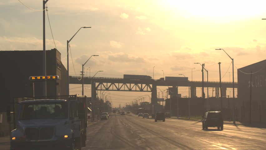 DETROIT, UNITED STATES - OCTOBER 17 2016: Cars driving on a busy highway under the overpass bridge, through the industrial zone at sunset. Dense traffic on streets of Detroit at golden light morning