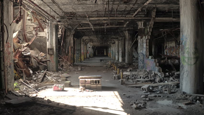 CLOSE UP: Destruction and debris in crumbling halls of decaying abandoned old Fisher Body Plant automotive factory, Detroit, America. Spooky demolished garage in big haunted industrial building in USA