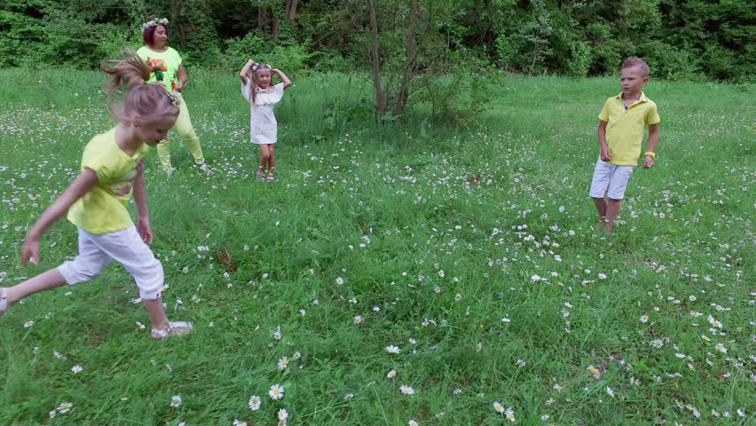 Children together with their mothers are playing with the ball on the chamomile meadow, near the forest. They have fun. Summer, outdoors, in the forest. Vacation with children | Shutterstock HD Video #28112626