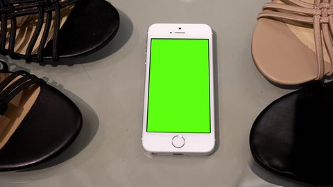 Coquitlam, BC, Canada - June 18, 2017 : Motion of display sandals and green screen phone on table for leisure concept with 4k resolution