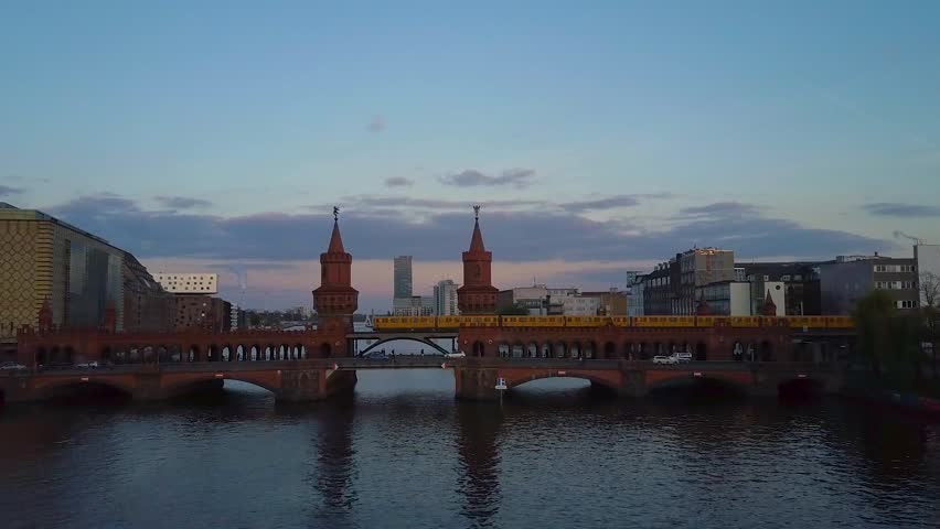 Aerial drone flight over the Spree river in Berlin with the Kreuzberg/Friedrichshain bridge and train/Ubahn in background.