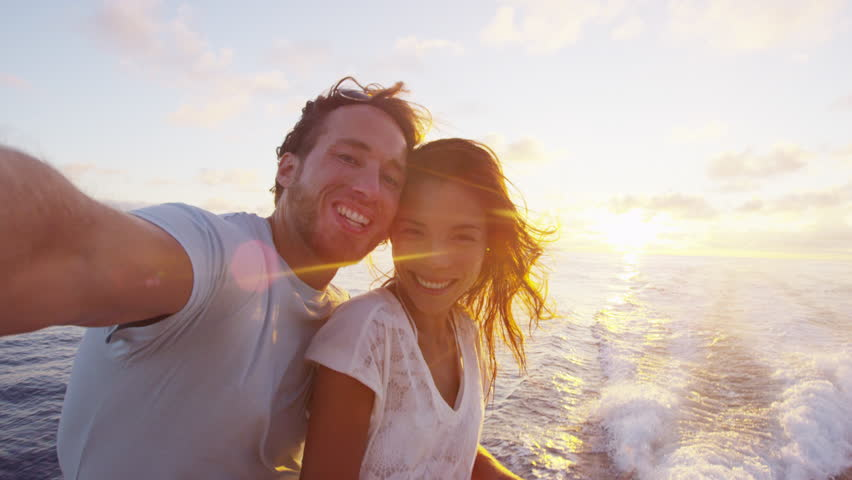 Selfie video - Romantic couple taking selfie video by sunset over the ocean on small cruise ship sailing on open sea. Woman and man taking cell phone photos on boat travel sailing during vacation.