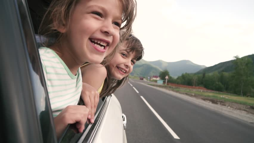Carefree children leaned out the car window and smiling. two little girls having fun in car. slow motion