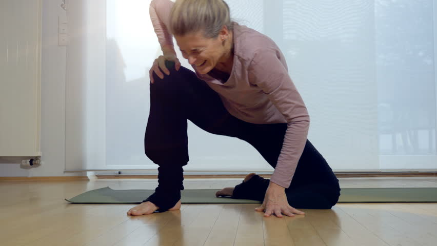 Woman feeling knee pain after standing up following yoga exercise. Full length.
