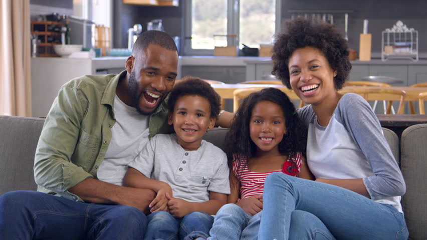 Portrait Of Family On Sofa In Open Plan Laughing Towards Camera #28165354