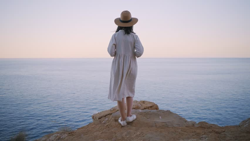 Rear view on shy and dreamy amish girl in simple white cotton dress and straw hat, standing on the edge of rock cliff and looking far away in ocean sea, waiting someone. Wind slightly swings her dress
