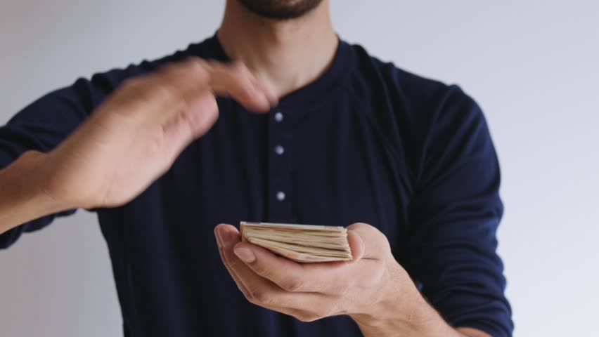 Slow motion of male hands of thin urban modern businessman in casual outfit making it rain after successful business deal in startup company