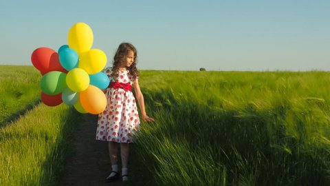 Little girl with balloons in a field of wheat. Happy child with balloons.
