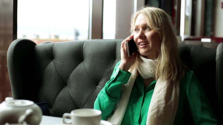 A girl is talking on a smartphone in a cafe. A woman is talking on a smartphone. | Shutterstock HD Video #28179391