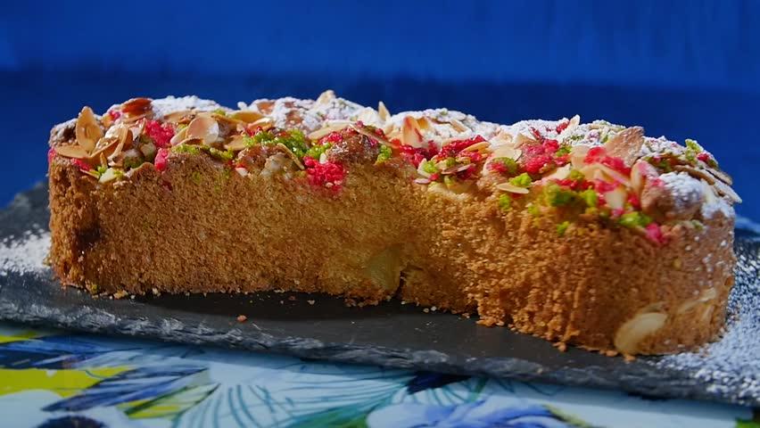 Beautiful cake. Piece of apple cake on dark blue background. Apple cake  with walnut shavings