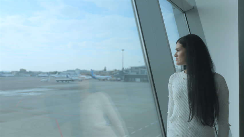 Dreamily girl stand near the window and looks on the runway with airplanes