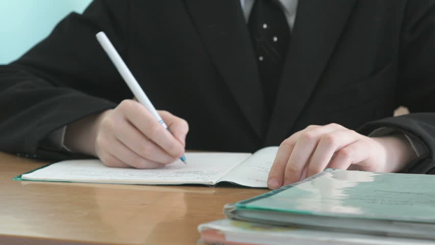 The student sits at a school desk and writes in a workbook with a ballpoint pen. Close-up Royalty-Free Stock Footage #28188898