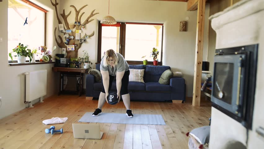 Attractive overweight woman at home working out with medicine ball. | Shutterstock HD Video #28194274