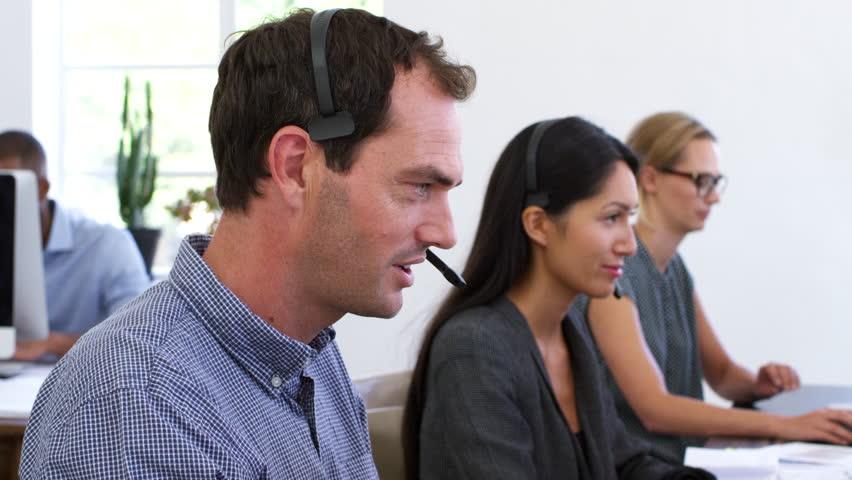 White man in headset smiles to camera in open plan office | Shutterstock HD Video #28199794