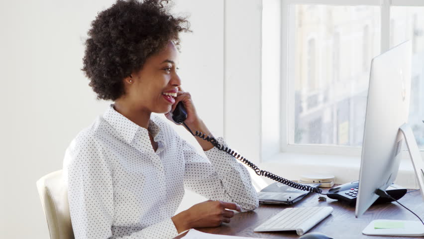 Young black woman on the phone in an office, slow motion