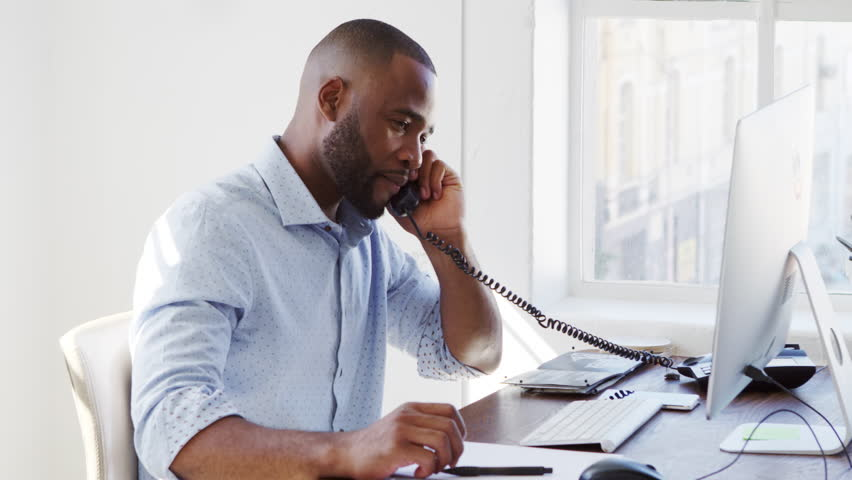 Young black man using phone and computer in office, close up