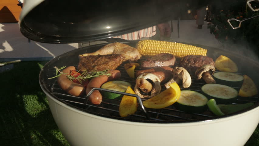opening kettle barbecue grill in garden