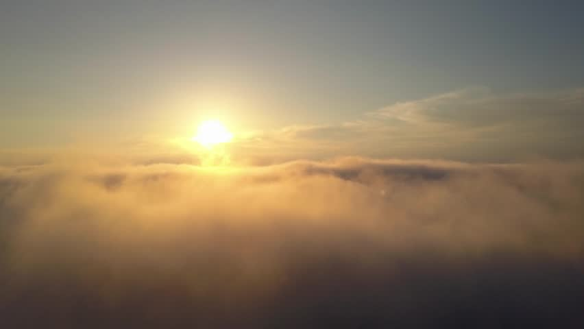 Aerial view rising above clouds and mist to see the sun | Shutterstock HD Video #28238032