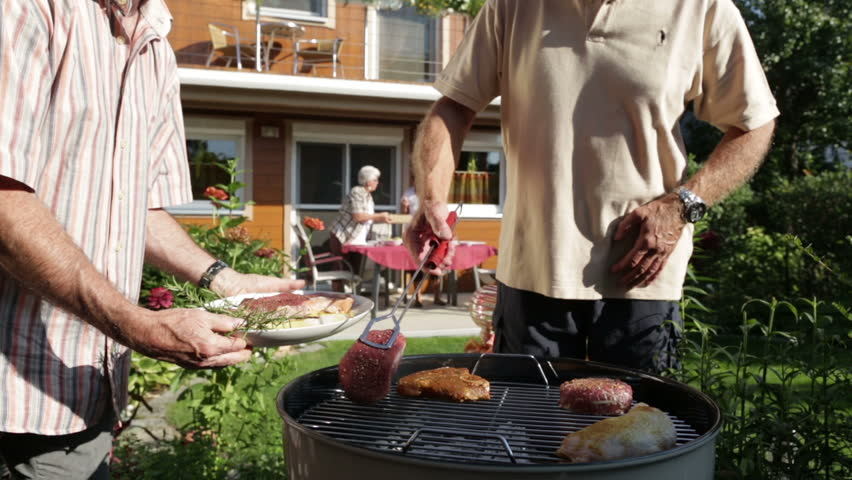 retirees putting beef on kettle barbecue in garden