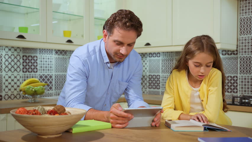 Attractive father helping his daughter with her homework at the kitchen using tablet. | Shutterstock HD Video #28244650