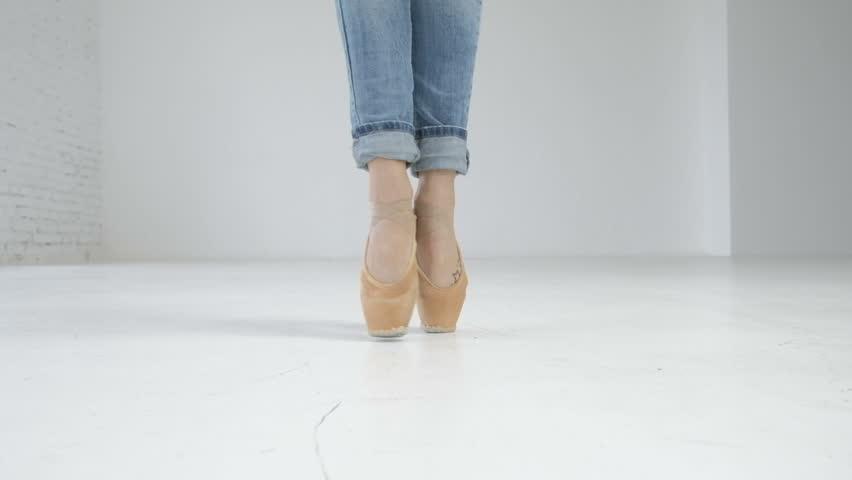 detail of ballet dancer''s feet. White hall. Ballerina in blue jeans.