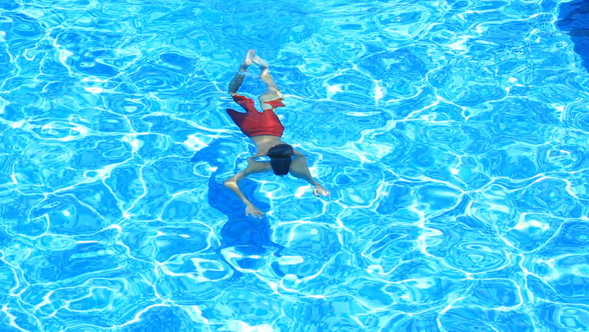 The child is swimming in the blue water of the pool. view from above. The boy dives under the water in the pool   Shutterstock HD Video #28268554