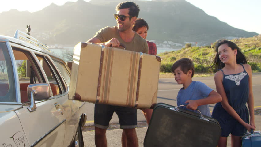 Family Loading Luggage Onto Car Roof Rack Ready For Road Trip #28274821
