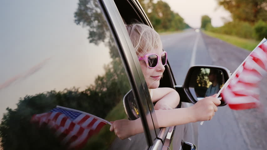 A blond little girl in pink glasses looks out the window of the car. In his hand holds the American flag