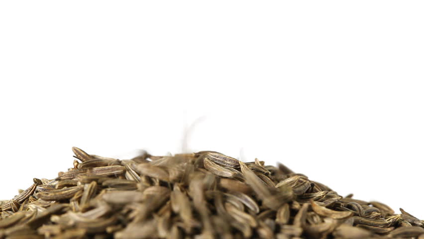 Cumin or caraway seeds falling and piling up isolated on white background