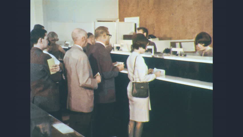 1960s: In bank, teller hands customer cash, customer counts. Man addresses viewer directly outside vault. Banker unlocks safe deposit box for customer. Customer banks with teller at drive-up window.