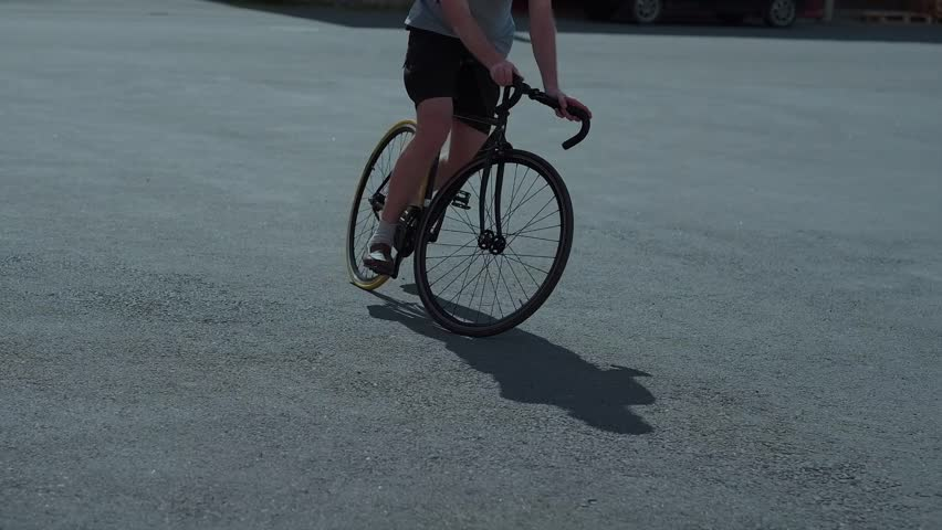 The Bearded Guy is Riding the Black Vintage Bike in Summer Day, in Black Shorts, a Green Cap, Glasses, Backpack, on the Background of the Trash Can | Shutterstock HD Video #28327927