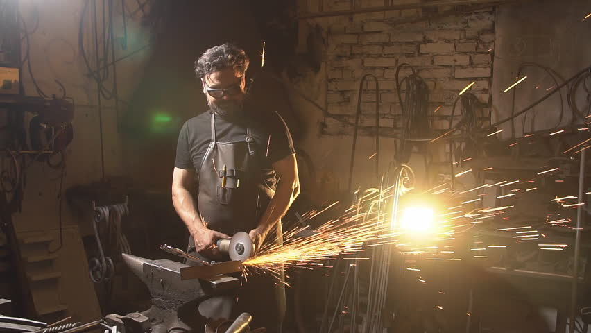 Sparks during cutting of metal angle grinder. blacksmith working in a workshop with metal. Worker using industrial grinder. slow motion
