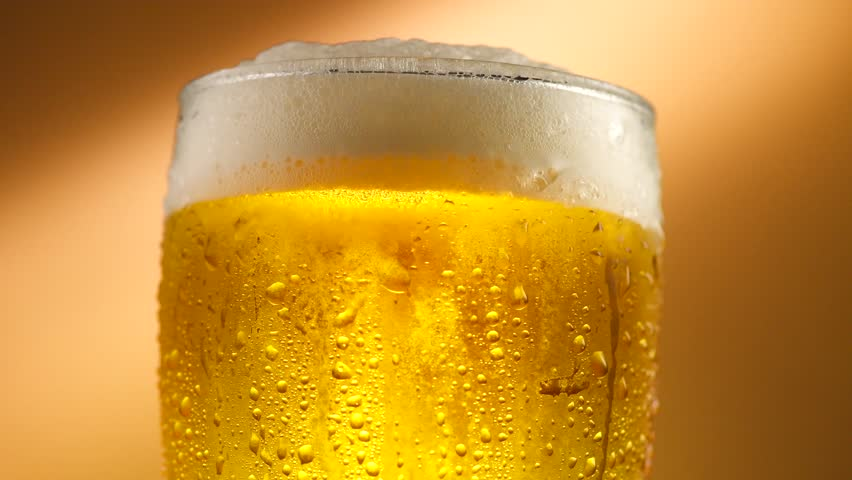 Cold Light Beer in a glass with water drops. Craft Beer close up. Rotation 360 degrees. 4K UHD video 3840x2160 #28337908