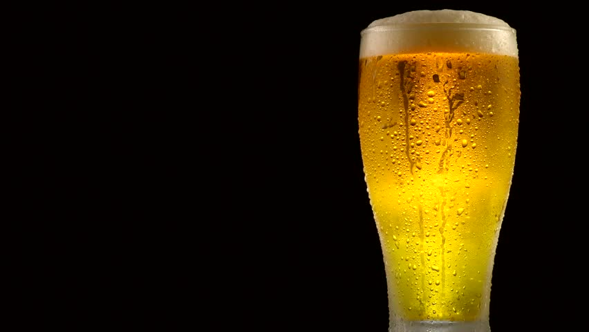 Cold Light Beer in a glass with water drops over matte black background, border design. Craft Beer close up. Copy space for your text. Rotation 360 degrees. 4K UHD video 3840x2160 #28372906