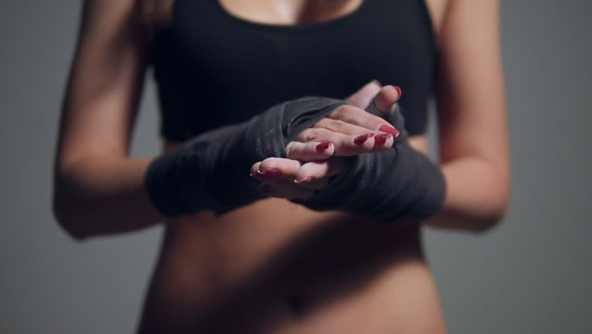 Closeup view of young beautiful fit woman dusting powder on her hands wrapped in boxing tapes as she prepares for a workout at the gym. Slowmotion shot