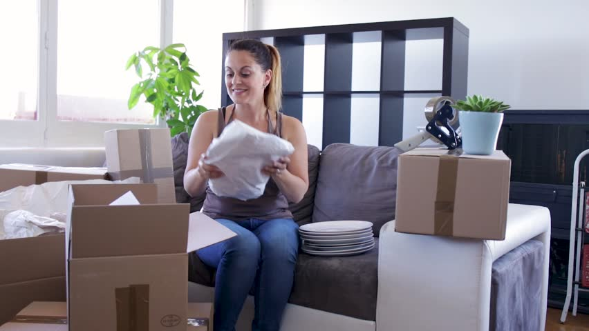 Moving concept Young woman smiles while preparing her moving cartons #28383379