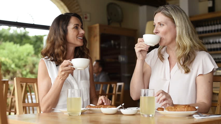 Two beautiful mature women holding cup of coffee and talking to each other in a cafeteria. Senior women in conversation while having breakfast. Happy middle aged friends meeting up for coffee.  #28383643