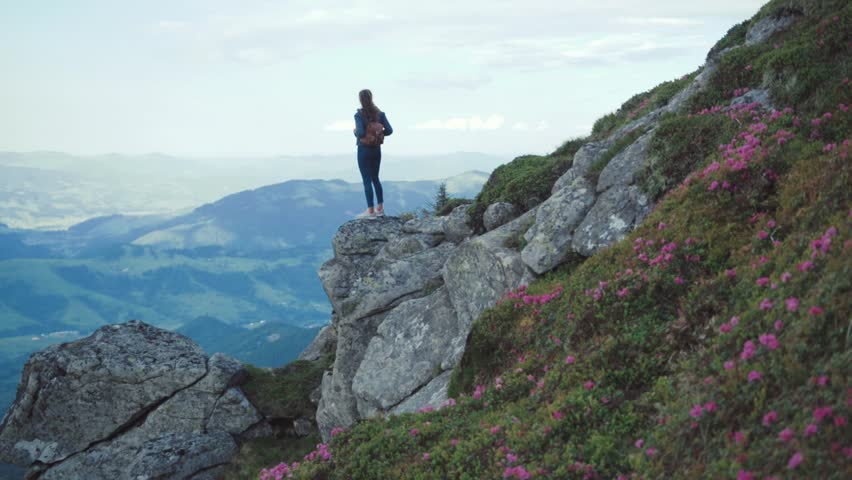 Young woman with a backpack in casual wear stands on the edge of a mountain cliff high above, looks around thrilled. Having fun, adventure time. Hiking alone. Beautiful scenery on the background. | Shutterstock HD Video #28385038