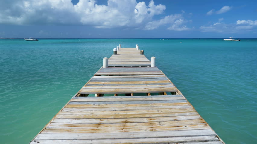 Perfect caribbean beach background with dock and boat and islands.