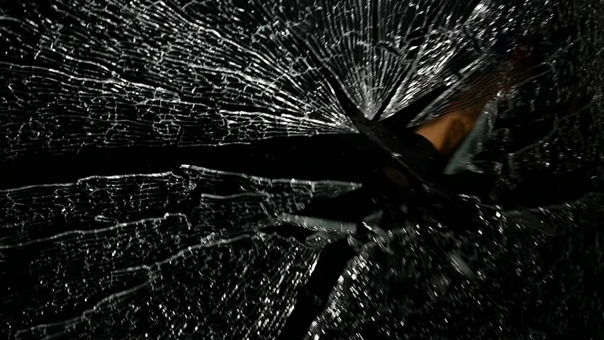 Brings a hammer to the glass and hits it, it crumbles into small pieces. Black background. Slow motion   Shutterstock HD Video #28401955