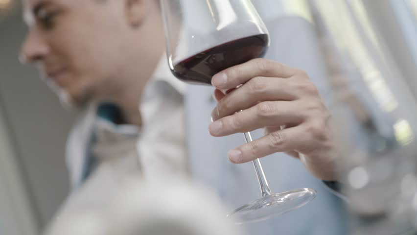 A glass of red wine in the man's hand. Concept evening in a restaurant, an aperitif. A businessman in a suit holds a glass with red wine and drinks it. Alcoholic beverage. | Shutterstock HD Video #28411678