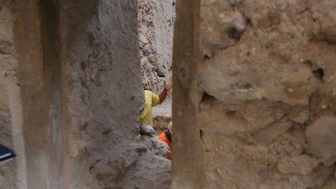 Archeologists working on dig of old village, solving problem, excavation site