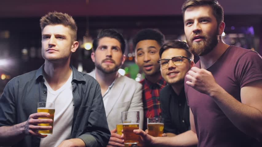 Concentrated five young men friends in bar watching football match while drinking beer