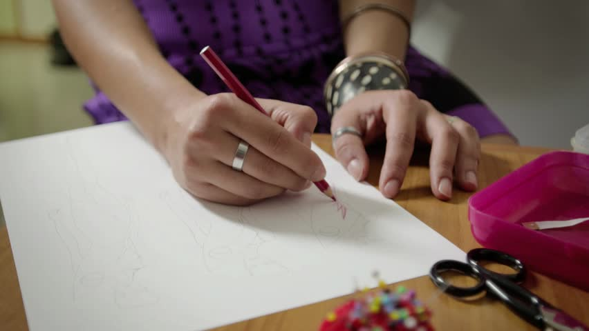 Female fashion designers drawing sketches for clothes in atelier. Sequence