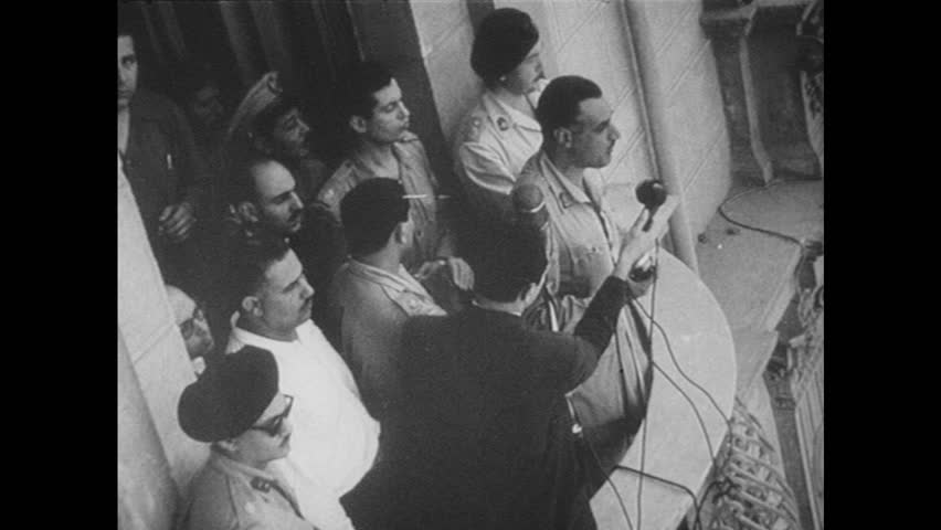 1960s: Gamal Abdel Nasser speaking from balcony. View of crowd. Soldier walking. Soldiers around wrecked car.