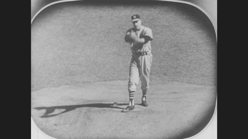 1950s: Baseball player on TV pitches. Batter hits ball and runs. Woman, girl and two boys watch baseball game on television. Players advance from second to third base, and third base to home plate.